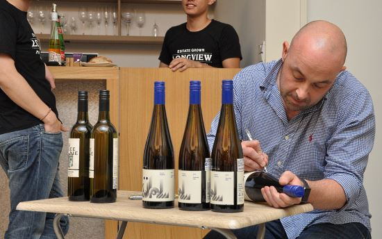 longview-vineyard-peter-signing-on-the-bottle